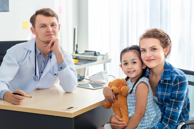 Pediatra (lekarz) mężczyzna, matka i córeczka uśmiechając się w szpitalu.