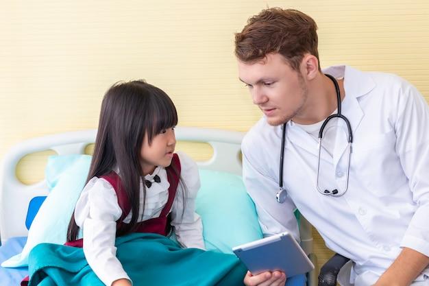 Pediatra mężczyzna nagrywa informację i bierze pastylkę z małą dziewczynką w szpitalu.