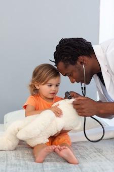 Pediatra mówi do małej dziewczynki