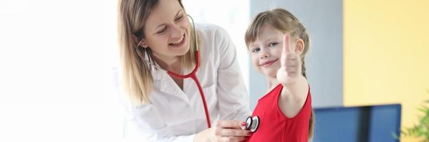 Pediatra słucha stetoskopem do serca małej dziewczynki. udana koncepcja leczenia