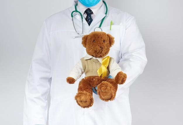 Pediatra w białym płaszczu i niebieskich lateksowych rękawiczkach trzyma brązowego misia