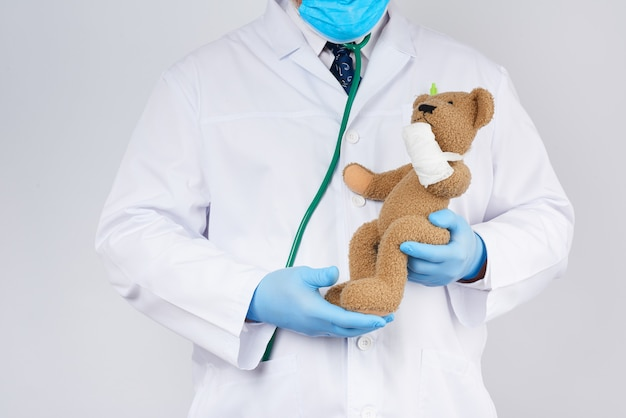 Pediatra w białym płaszczu, niebieskich lateksowych rękawiczkach trzyma brązowego misia z zabandażowaną łapą