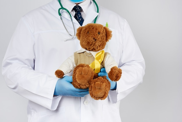 Pediatra w białym płaszczu, niebieskich lateksowych rękawiczkach trzyma brązowego misia z żółtą wstążką