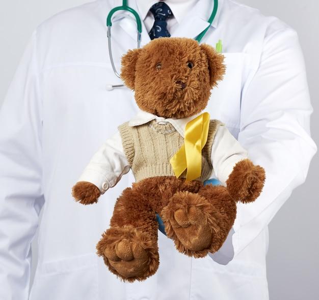 Pediatra w białym płaszczu, niebieskie lateksowe rękawiczki trzyma brązowego misia z żółtą wstążką na swetrze, koncepcja walki z rakiem dziecięcym
