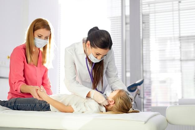 Pediatra w masce przeprowadza badanie kontrolne stanu zdrowia dziecka, podczas epidemii covid-19 na całym świecie, matka siedzi wspierając
