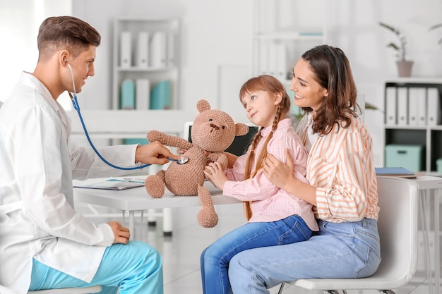 Pediatra z zabawką pokazujący dziewczynce, jak używać stetoskopu w klinice