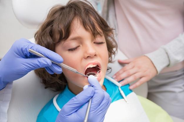 Pediatryczny dentysta egzamininuje chłopiec zęby z jego matką