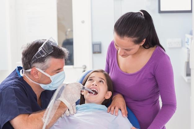 Pediatryczny dentysta egzamininuje młodego pacjenta z jej matką