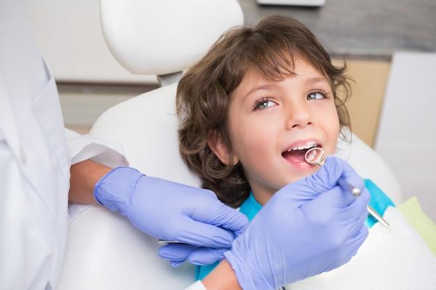 Pediatryczny dentysta egzamininuje troszkę chłopiec zęby w krzesło dentystów