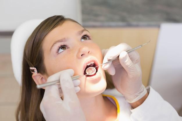 Pediatryczny dentysta egzamininuje troszkę dziewczyn zęby w krzesło dentystów