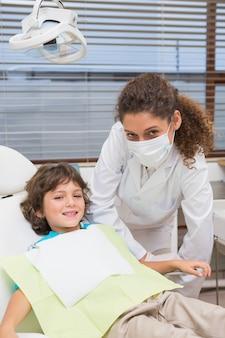 Pediatryczny dentysta ono uśmiecha się z chłopiec w krześle