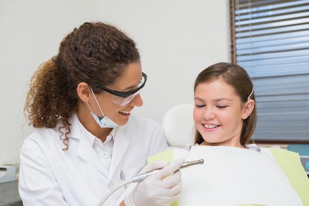Pediatryczny dentysta ono uśmiecha się z małą dziewczynką w krześle