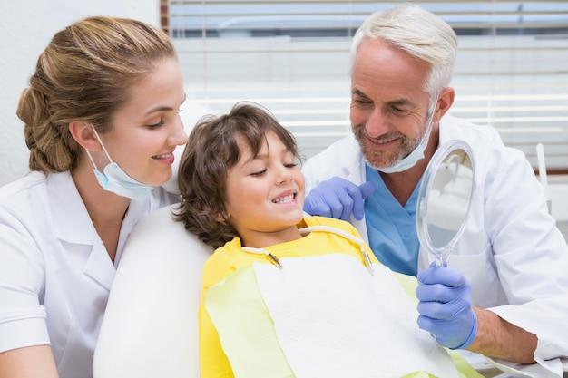 Pediatryczny dentysta pokazuje chłopiec jego zęby w lustrze
