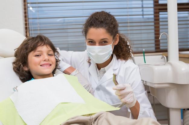Pediatryczny dentysta pokazuje chłopiec w krześle świder