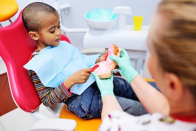 Pediatryczny dentysta uczy dziecko w afroamerykanie, które siedzi na fotelu dentystycznym, aby prawidłowo myć zęby. dentysta dziecięcy