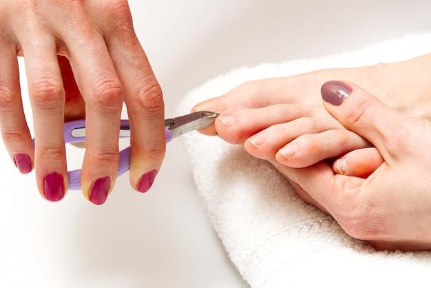 Pedicure domowy. zabieg pielęgnacyjny stóp i paznokci. młoda kobieta robi pedicure'owi w domu.