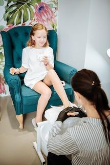 Pedicure i herbata. stylowa śliczna blondynka nastolatka pije herbatę siedzi w fotelu o pedicure
