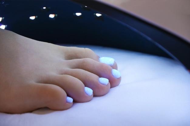 Pedicure medyczny. lampa uv do suszenia lakieru i żelu. lakier do paznokci świeci od światła ultrafioletowego