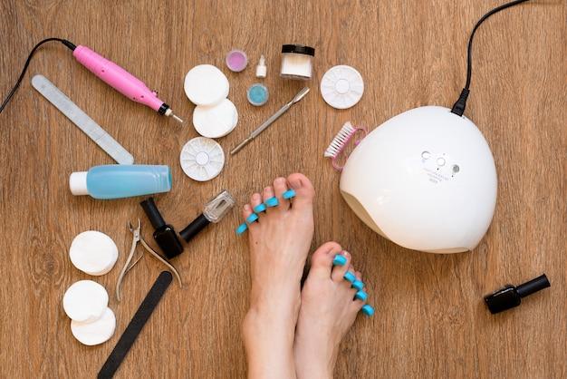 Pedicure w domu przy użyciu lakieru do paznokci i lamp uv, pilników i nożyczek. dbanie o siebie i nie wychodzenie z domu. proces malowania paznokci i suszenia w lampie uv. widok z góry, układ płaski.