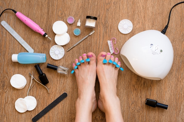 Pedicure w domu z użyciem lakieru do paznokci i lamp uv, pilników i nożyczek