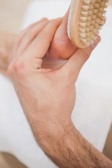 Pedicurist szczotkowanie klientów stóp
