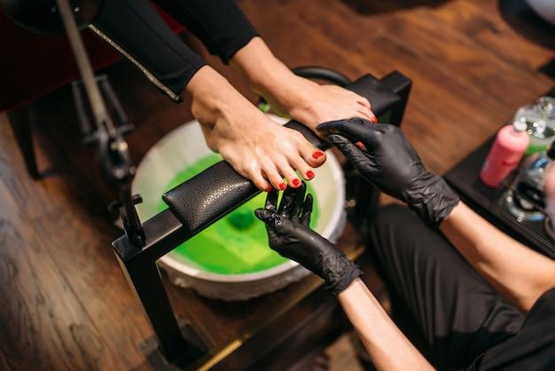 Pedicurzystka w czarnych rękawiczkach robi zabieg kosmetyczny z kąpielą pedicure