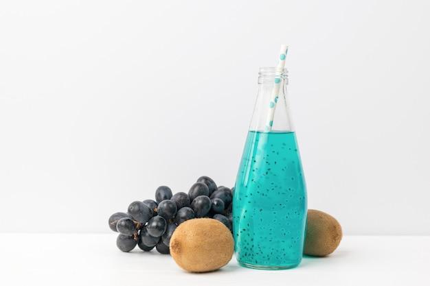 Pędzel ciemnych winogron, kiwi i butelka egzotycznego koktajlu na jasnym. egzotyczny orzeźwiający napój.
