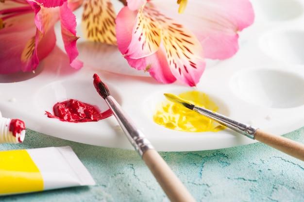 Pędzel, czerwona, żółta farba akwarelowa z wiosennymi kwiatami