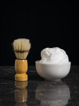 Pędzel do golenia z miską pianki do golenia na kamiennym tle. zestaw do pielęgnacji męskiej twarzy.
