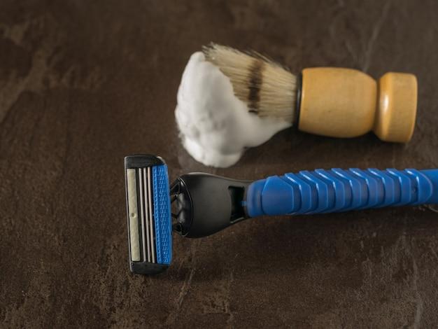 Pędzel do golenia z pianką do golenia i niebieska brzytwa na kamiennej powierzchni. zestaw do pielęgnacji męskiej twarzy. leżał płasko.