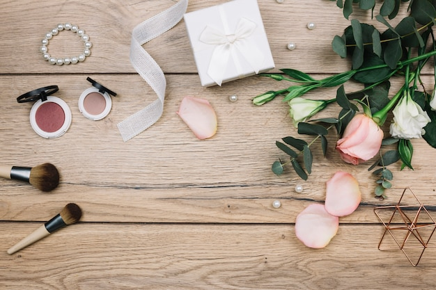 Pędzel do makijażu; kompaktowy puder do twarzy; perły; pudełko na prezent; róża i eustoma kwiaty na drewniane biurko