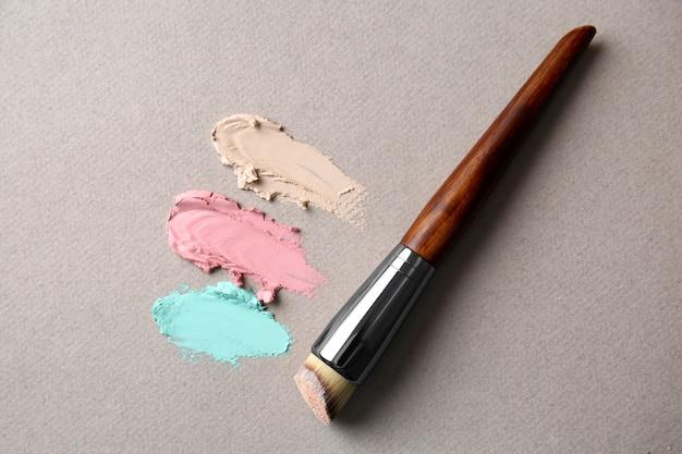 Pędzel do makijażu z produktami kosmetycznymi na szarej powierzchni