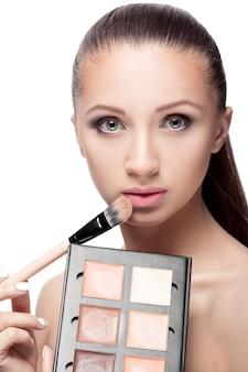 Pędzel do modelowania twarzy. naturalny makijaż dla idealnej skóry. wizażystka robi makijaż pędzlem.