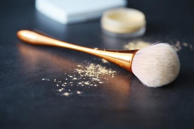 Pędzel do pudru i makijażu. brązowy proszek na tle. produkty do makijażu. koncepcja stylu.