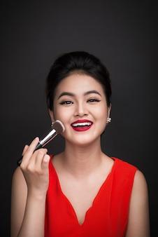 Pędzel do pudru kosmetycznego. azjatka nakładająca róż na policzki z perfekcyjnym makijażem i czerwonymi ustami