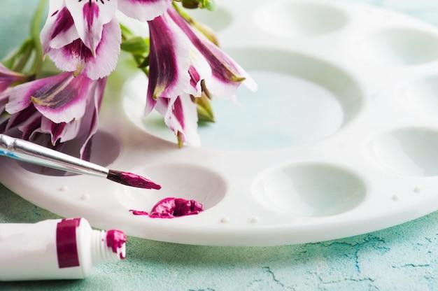 Pędzel, fioletowa farba akwarelowa z wiosennymi kwiatami