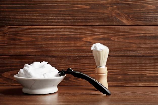 Pędzel fryzjerski, pianka do golenia i maszynka do golenia dla mężczyzny na stole