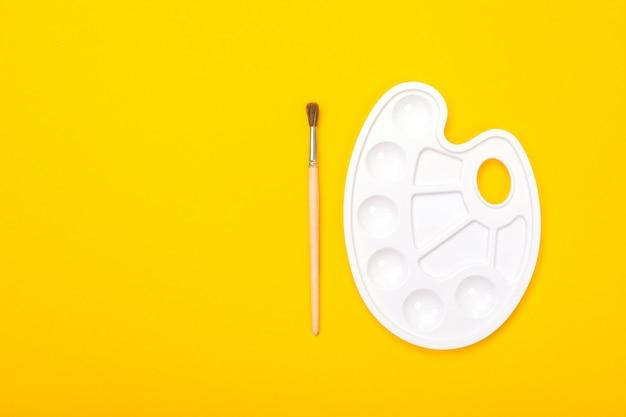 Pędzel i palety leżą na białym tle na żółty