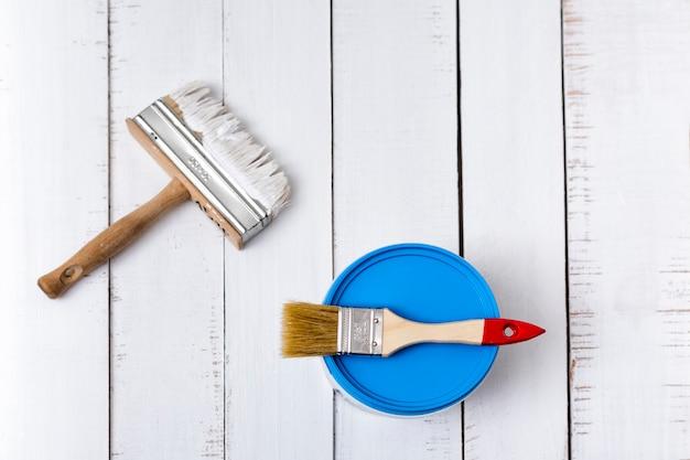 Pędzel i wiadro z farbą na białych, odrapanych drewnianych deskach.