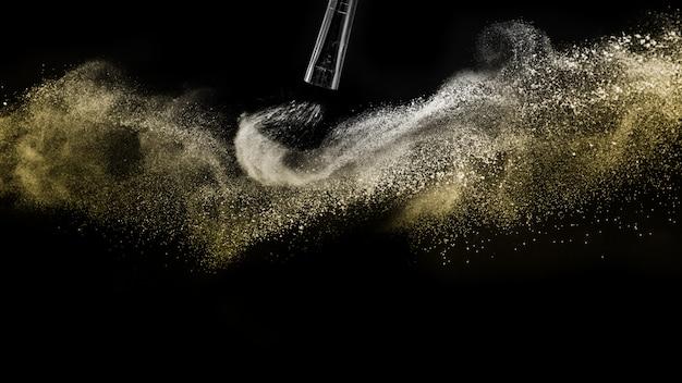 Pędzel kosmetyczny ze złotym kosmetykiem w proszku