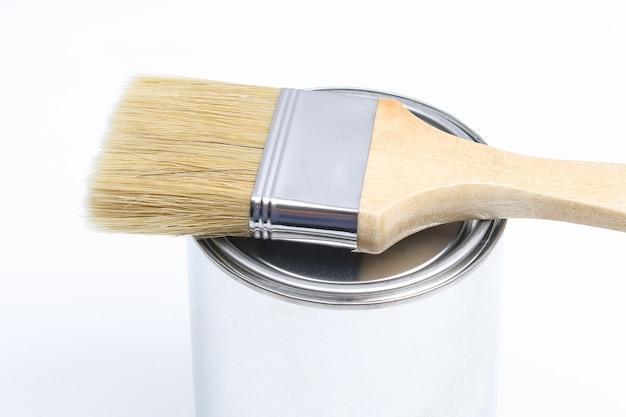 Pędzel leży na puszce z białą farbą na białej powierzchni