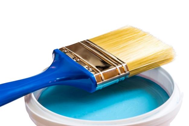 Pędzel na puszce niebieskiej farby na białym