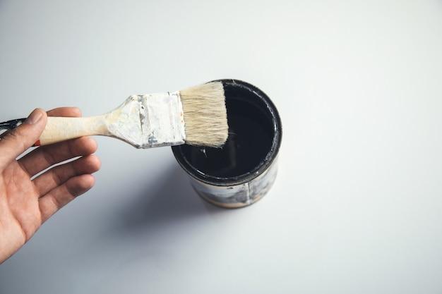 Pędzel ręczny człowieka na farbie na białym tle