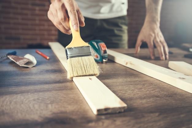 Pędzel w dłoni i malowanie na drewnie