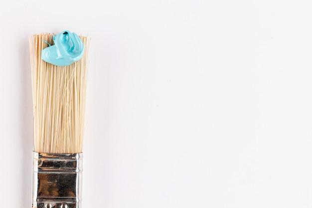 Pędzel z niebieską farbą i białym tłem
