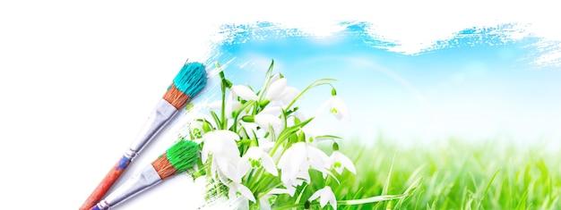 Pędzel z niebieską farbą na niebie i zielonym polu.