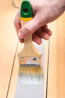 Pędzel z puszką do malowania w dłoni. mężczyzna maluje drewniane deski szarym pędzlem.