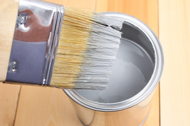 Pędzel z puszką do malowania w dłoni.
