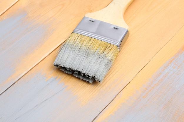 Pędzel z puszki maluje na drewnianych deskach szarym pędzlem