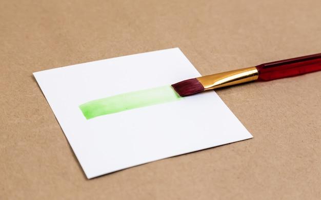 Pędzel z rozmazem zielonej farby. rozmaz żywej zielonej farby z pędzla na kartce białego papieru